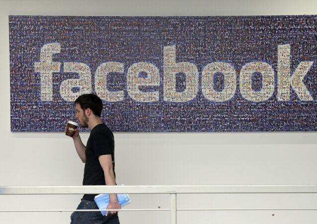 Člověk na pozadí loga Facebooku