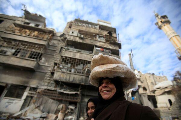 Žena nese chléb ve zničené čtvrti Aleppa - Sputnik Česká republika