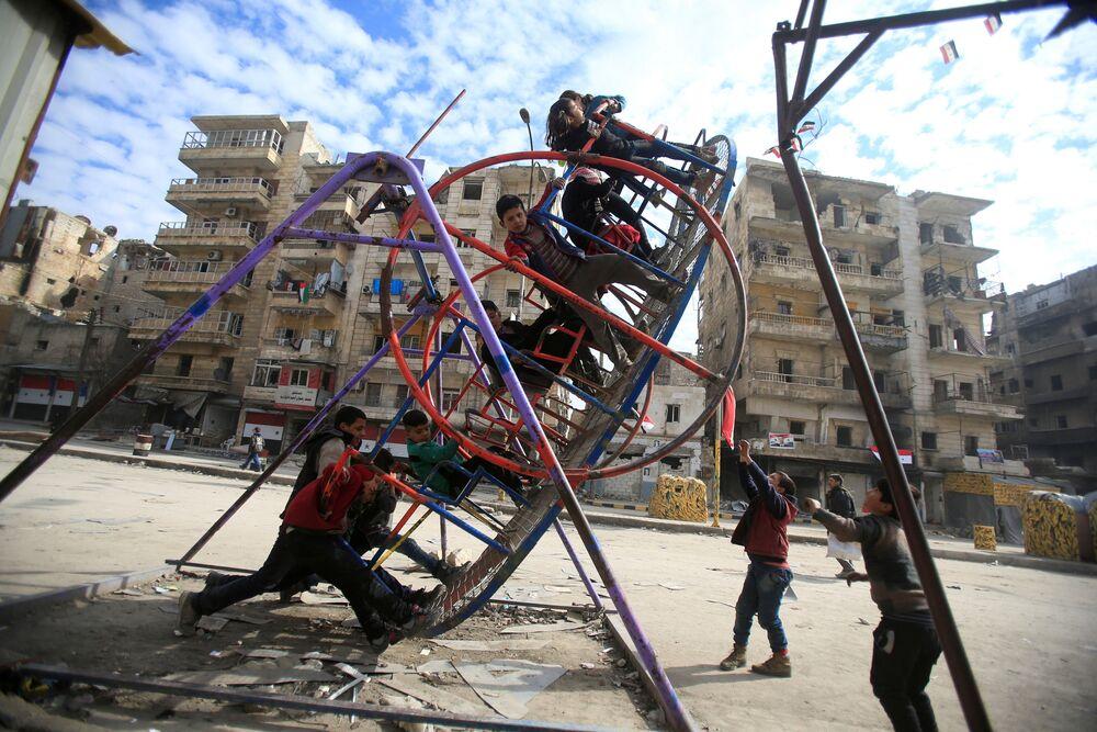 Děti na houpačce ve zničené čtvrti Aleppa