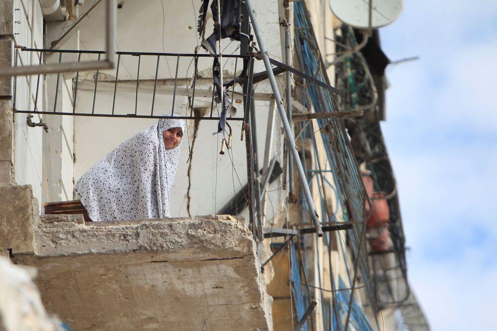 Žena na zničeném balkonu v Aleppu