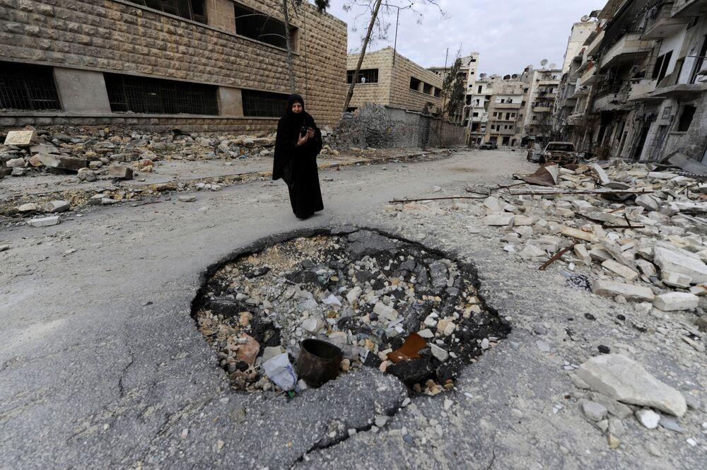 Žena fotografuje zničenou čtvrť v Aleppu