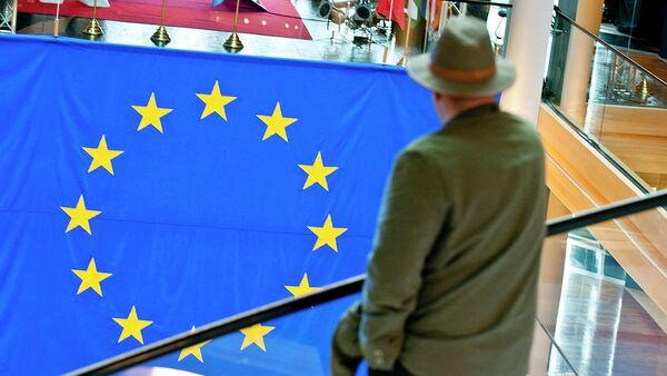 Muž se dívá na vlajku EU - Sputnik Česká republika