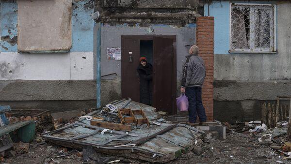 Místní obyvatelé u vchodu zničené budovy v Kyjevské čtvrti Doněcku - Sputnik Česká republika