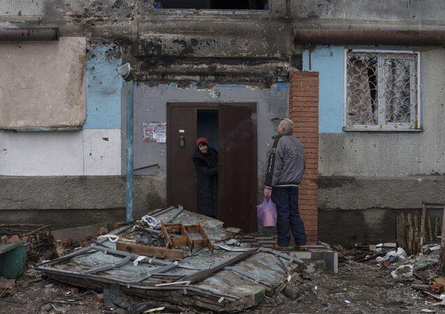 Místní obyvatelé u vchodu zničené budovy v Kyjevské čtvrti Doněcku