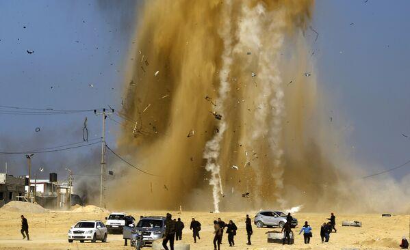 Palestinci se schovávají do úkrytu z místa výbuchu po leteckém útoku, Pásmo Gazy - Sputnik Česká republika