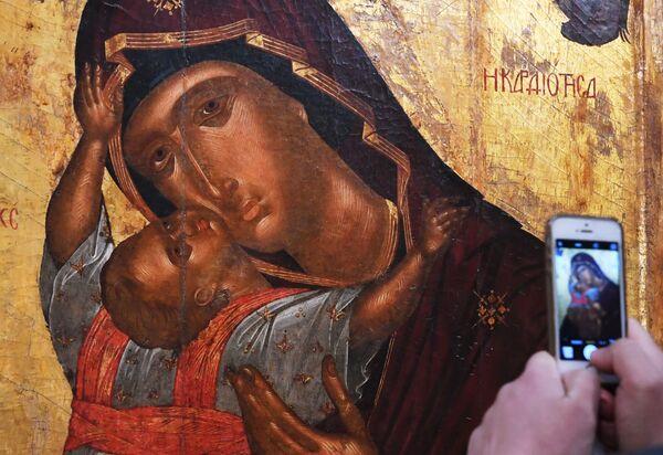 Návštěvník fotografuje ikonu Matky Boží s dítětem na otevření výstavy Byzantské skvosty v Tretjakovské galerii - Sputnik Česká republika
