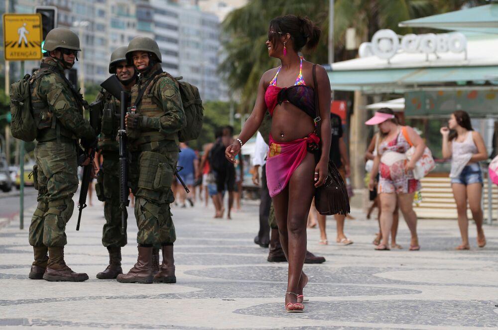 Brazilská námořní patrola a dívka na pláži Copacabana před karnevalem v Riu de Janeiru