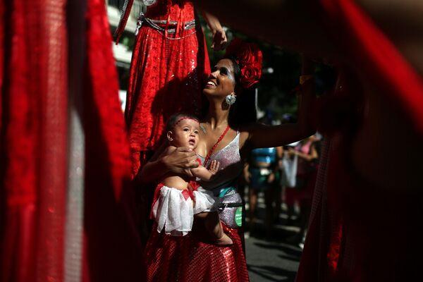Dívka s dítětem v náručí během zábavy před karnevalem v Riu de Janeiru - Sputnik Česká republika