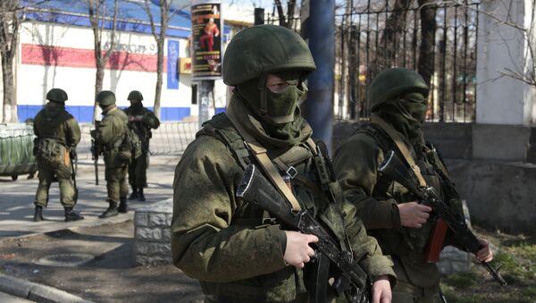 Lidé ve vojenském stejnokroji v Simferopolu - Sputnik Česká republika