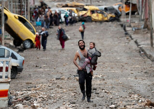 Muž s dcerou v náručí prchá z čtvrti Mosulu ovládané Islámským státem (IS, zakázaná v RF)