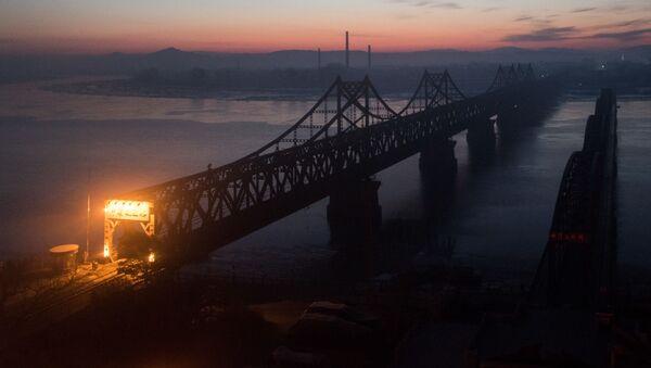 Рассвет над мостом у реки Ялуцзян на границе между Китаем и КНДР - Sputnik Česká republika