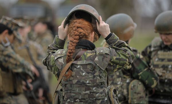 Rumunská vojenská příslušnice si upravuje přilbu na cvičení spolu s americkými vojačkami na rumunském pobřeží Černého moře - Sputnik Česká republika