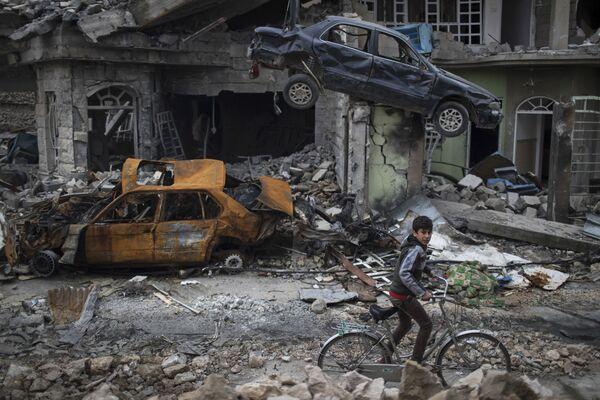 Chlapec na kole v osvobozené čtvrti na západě Mosulu, Irák - Sputnik Česká republika