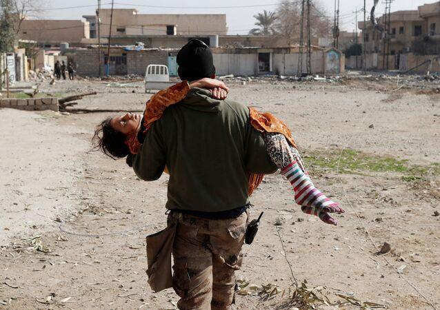 Irácký voják nese zraněnou dívku