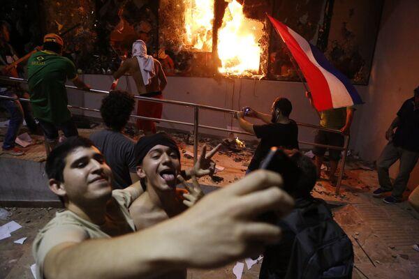 Muži se fotografují naproti budově Kongresu během srážek s policií po volbách v městě Asunción, Paraguay - Sputnik Česká republika