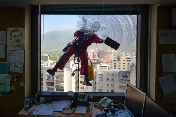 Umývač oken pracuje na jedné z budov v Caracasu - Sputnik Česká republika