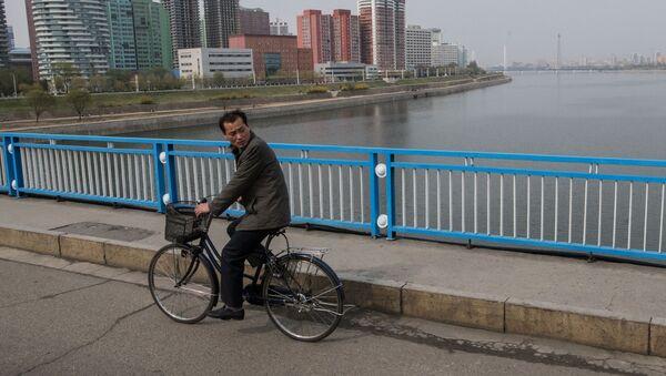 Muž jede na kole v Pchjongjangu - Sputnik Česká republika