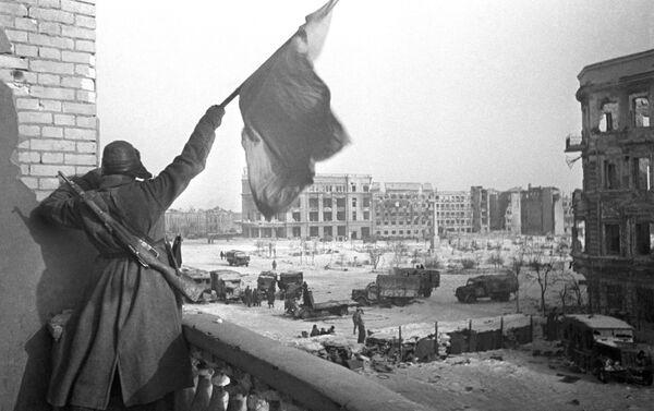 Rudá vlajka nad náměstím Padlých bojovníků v osvobozeném Stalingradu. Na pozadí je budova obchodního domu, kde byl zajat štáb 6. armády Wehrmachtu v čele s polním maršálem Paulusem - Sputnik Česká republika