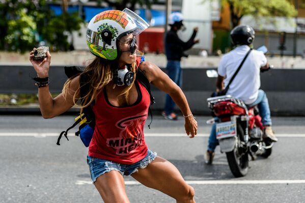 Dívka s kamenem na protivládní akci v Den práce v Caracasu, Venezuela - Sputnik Česká republika