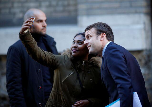 Kandidát na prezidenta Francie Emmanuel Macron dělá selfii s ctitelkou