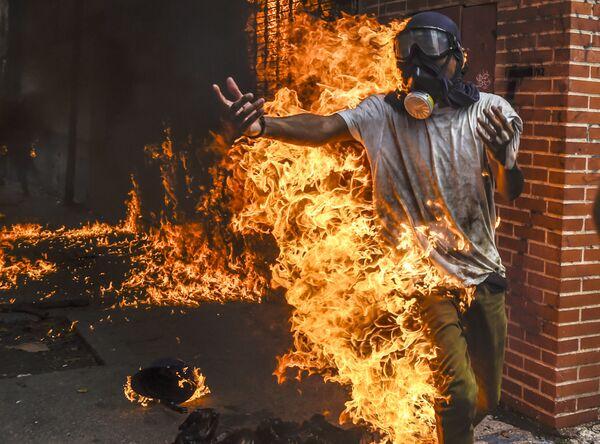 Demonstrant hoří v důsledku výbuchu benzínové nádrže motorky během protestů ve Venezuele - Sputnik Česká republika