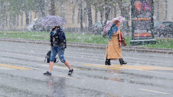 Chodci přecházejí ulici v Moskvě během sněžení - Sputnik Česká republika