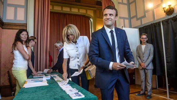 Francouzský prezident Emmanuel Macron a jeho žena během volebního hlasování - Sputnik Česká republika