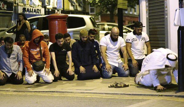 Věřící se modlí na místě útoku dodávky na lidi u mešity na severu Londýna - Sputnik Česká republika