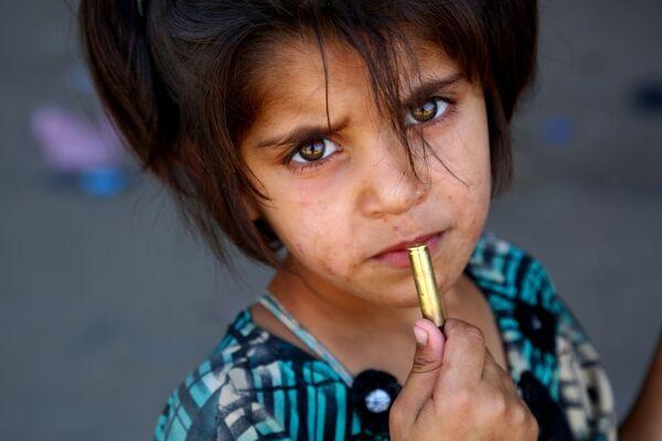 Děvčátko s nábojem v ruce nedaleko syrské Rakky - Sputnik Česká republika