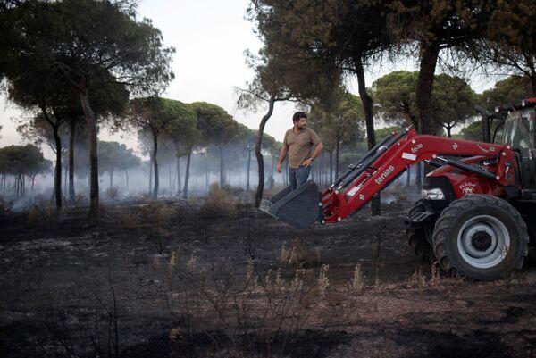 Muž na traktoru pomáhá hasit lesní požár na jihu Španělska - Sputnik Česká republika