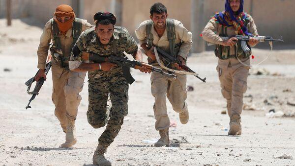 Kurdští bojovníci z Oddílu národní sebeobrany běží po městě Rakka, Sýrie - Sputnik Česká republika