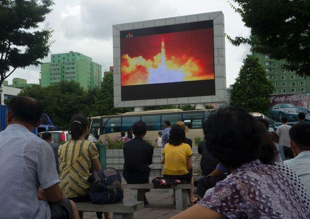 Na plátnu ukazují zprávy o startu rakety v KLDR