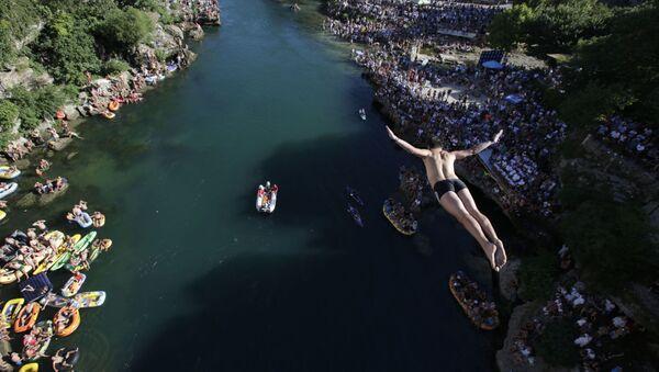Skokan na každoročním festivalu skoků z mostu v Mostaru, Bosna a Hercegovina - Sputnik Česká republika