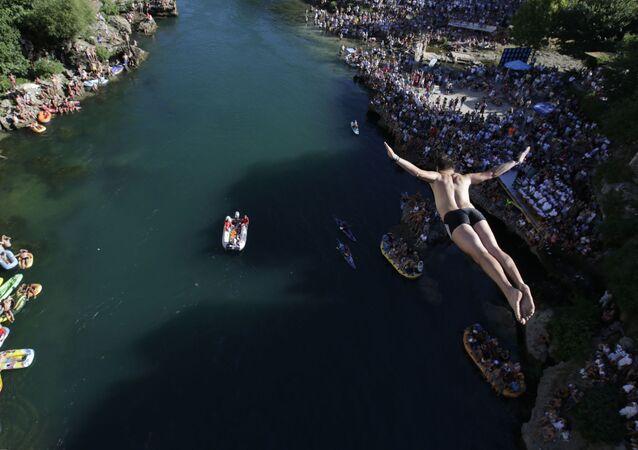 Skokan na každoročním festivalu skoků z mostu v Mostaru, Bosna a Hercegovina
