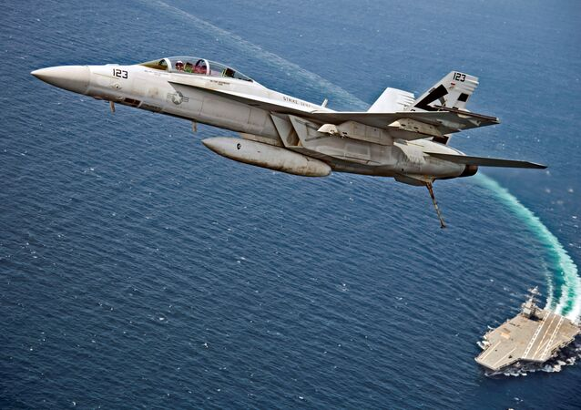 Americký stíhací bombardér F/A-18F Super Hornet letí nad letadlovou lodí Gerald R. Ford během testování magnetického katapultu pro letadlové lodě EMALS v Atlantiku