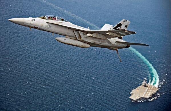 Americký stíhací bombardér F/A-18F Super Hornet letí nad letadlovou lodí Gerald R. Ford během testování magnetického katapultu pro letadlové lodě EMALS v Atlantiku - Sputnik Česká republika