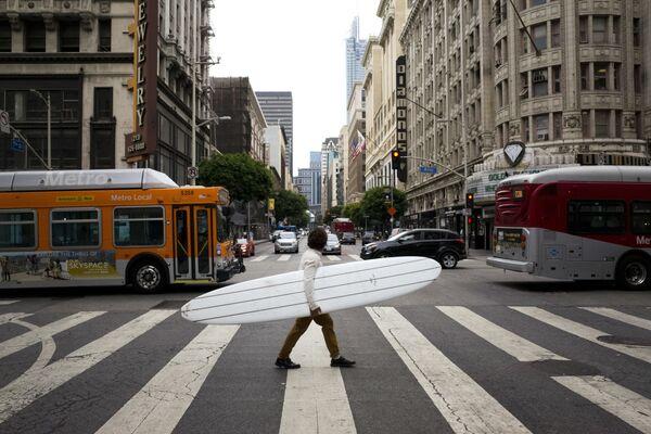 Muž se surfingovým prknem na ulici v Los Angeles, USA - Sputnik Česká republika