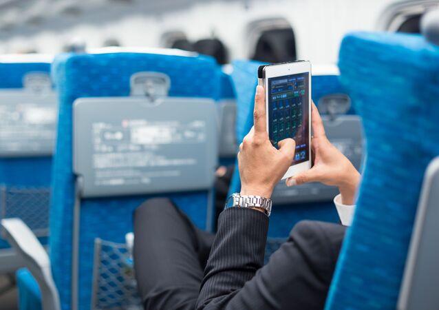 Muž s telefonem v letadle. Ilustrační foto