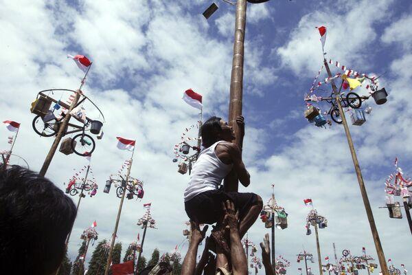 Muž se snaží vyšplhat na sloup, aby vyhrál kolo během oslav Dne nezávislosti na Bali, Indonésie - Sputnik Česká republika