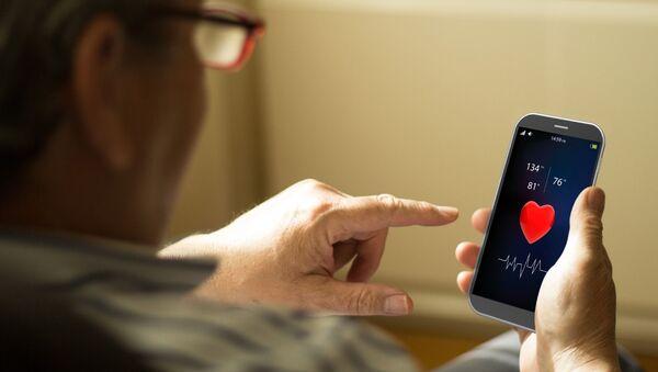 Postarší muž používá aplikaci M-Health na telefonu - Sputnik Česká republika