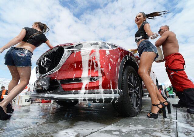 Modelky u automobilu na panelu Mazda během autosalonu Vladivostok International Autosalon