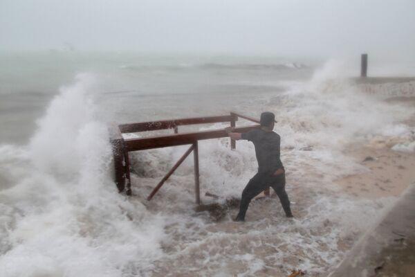 Muž se pokouší dostat z oceánu stůl, který moře odneslo z restaurace během uragánu Maria v Punta Cana, Dominikánská republika - Sputnik Česká republika