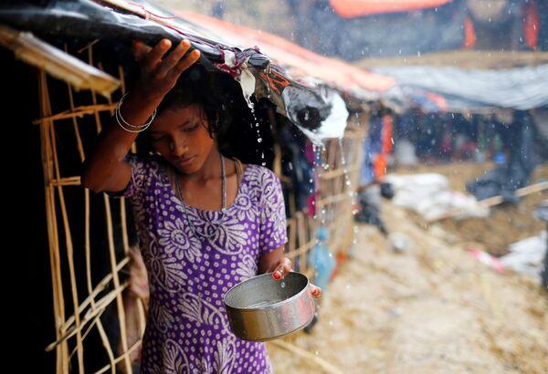 Dívka patřící k běžencům z etnika Rohingyů sbírá dešťovou vodu v přechodném táboře ve městě Cox's Bazar v Bangladéši - Sputnik Česká republika