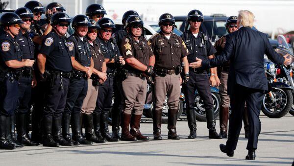 Americký prezident Donald Trump vítá důstojníky motorkové policie, kteří ho doprovázeli na letiště Indianopolisu - Sputnik Česká republika