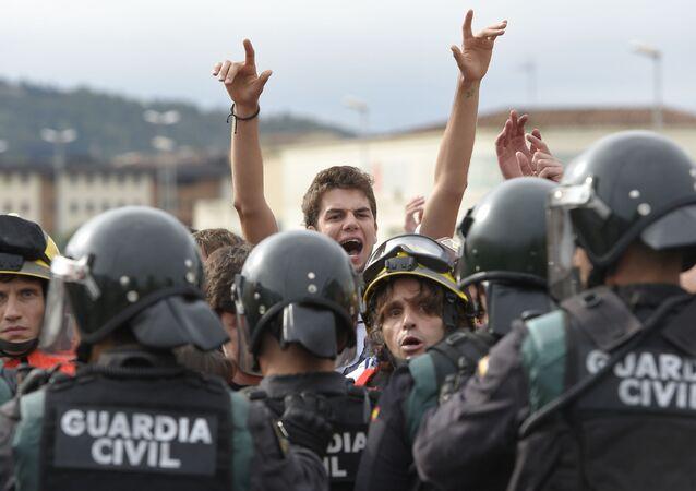 Španělští požárníci a příslušníci gardy zadržují lidi u volebních okrsků v den referenda o nezávislosti v Katalánsku