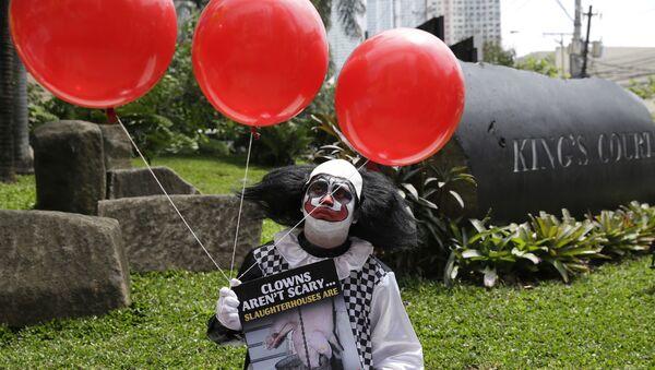 Klaun s rudými balónky se účastní demonstrace na stanici metra v Manile - Sputnik Česká republika