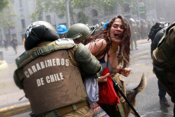Potyčka demonstrantů s policií během protestní akce v Den Kolumba v Santiagu, Chile - Sputnik Česká republika