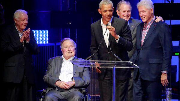 Setkání bývalých prezidentů USA na koncertu v Texasu. George Bush straší na vozíčku uprostřed. - Sputnik Česká republika