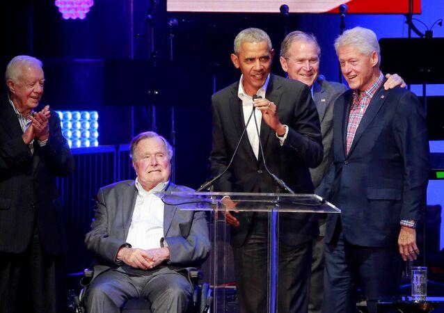 Setkání bývalých prezidentů USA na koncertu v Texasu. George Bush straší na vozíčku uprostřed.