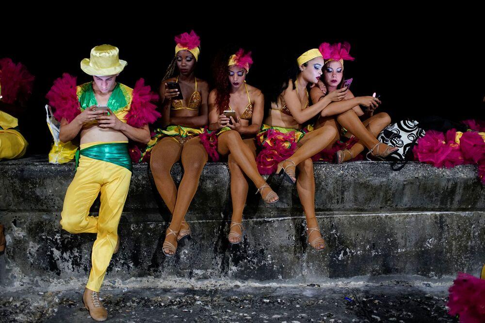 Tanečníci s telefony před začátkem vystoupení na karnevalu v Havaně, Kuba